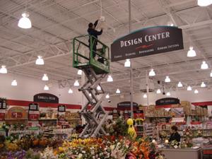 Employee on scaffold repairing lights
